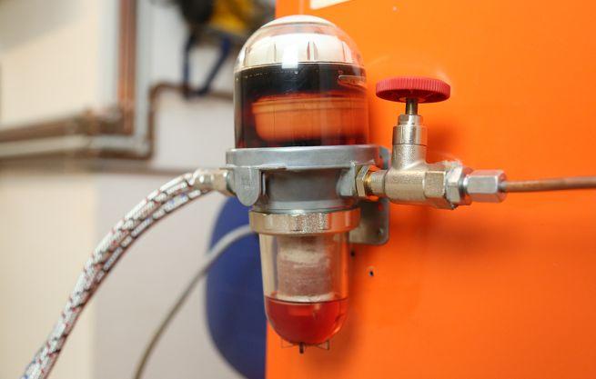 Ein zwischen Heizöltank und Ölheizung angebrachter Brennstofffilter mit Leitungen für den Zulauf und Ablauf.