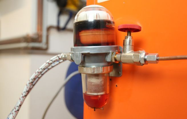 A fuel filter installed between the fuel oil tank and the oil heater, with pipes for the inlet and outlet.
